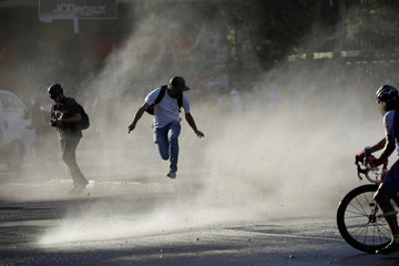 A protester runs away as a water cannon is sprayed during a protest against Chile's government in Santiago
