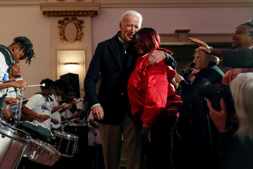 Democratic 2020 U.S. presidential candidate and former U.S. Vice President Joe Biden embraces a coach from the Union Baptist Crusaders drill team look on during an event at the Brown Derby Ballroom in Waterloo, Iowa