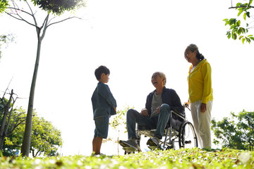 asian grandparents and grandson enjoying nature in park