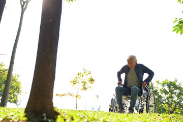 asian old man trying to get up from wheelchair