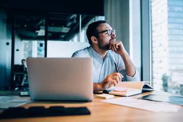 Thinking man making notes in office