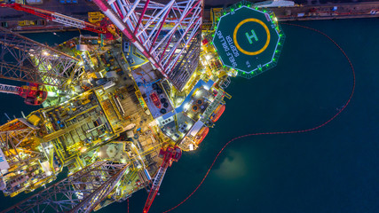 Aerial view construction offshore jack up rig drill at night, Offshore crane crude oil rig drilling platform.
