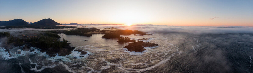 Wall Mural - Ucluelet, Vancouver Island, British Columbia, Canada. Aerial Panoramic View of a Small Town near Tofino on a Rocky Pacific Ocean Coast during a cloudy  and colorful morning sunrise.