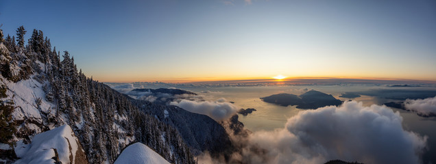St Mark's Summit, in Howe Sound, North of Vancouver, British Columbia, Canada. Panoramic Canadian Mountain Landscape View from the Peak during cloudy winter sunset.