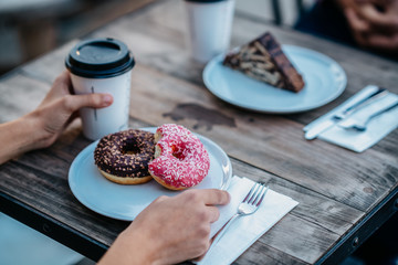 a couple is eating in a cafe delicious pastry and drink coffee
