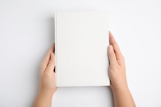 Woman holding book with blank cover on white background, top view