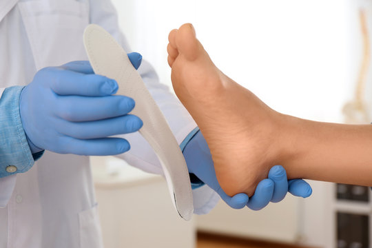 Male orthopedist fitting insole on patient's foot in clinic, closeup