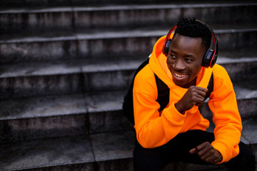 smiling african-american man in stylish orange hoodie sweatshirt in wireless headphones listening music and sitting on stairs. copy space