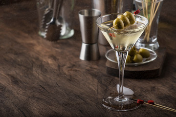 Classic Martini vodka cocktail, with dry vermouth, vodka and green olives, bar tools, vintage wood bar counter, selective focus