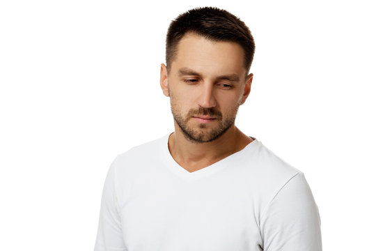 portrait of sad bearded man in casual white shirt isolated on white background