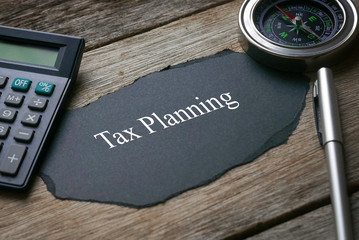 Compass,calculator,pen and a piece of black paper written with Tax Planning on wooden background. Wall mural