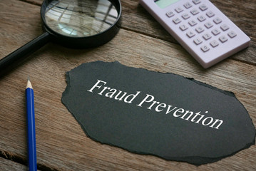 Calculator,magnifying glass,pencil and piece of black paper written with Fraud Prevention on wooden background.