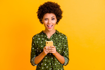 Portrait of excited crazy afro american girl hold smart phone use read social network news wear stylish green bright clothing isolated over yellow color background