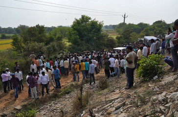 People gather at the site where police shot dead four men suspected of raping and killing a 27-year-old veterinarian, in Chatanpally on the outskirts of Shadnagar town