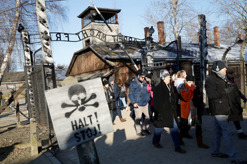 """People walk past the """"Arbeit Macht Frei"""" gate at the former Nazi German concentration and extermination camp Auschwitz in Oswiecim"""