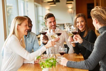 Group of friends drink wine and celebrate