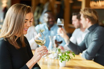 Woman drinking a glass of white wine in the restaurant