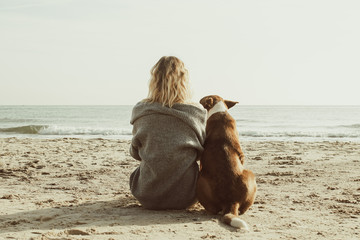 Young woman sitting and hugging dog on the beach. Friendship concept - woman and dog sitting together on a beach and enjoying sunrise. Back view colorized image
