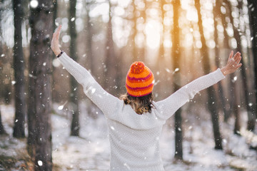 Young woman in an orange cap enjoying the sunny weather outdoors after first snow in the woods.