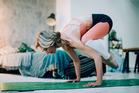 Attractive Caucasian woman in trendy tracksuit doing arm balance exercise for training muscles, young healthy female with perfect body shape doing bakasana or crow yoga pose during morning workout