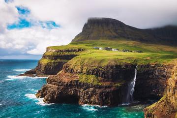 Wall Mural - Gasadalur village and its waterfall under strong wind, Faroe Islands, Denmark