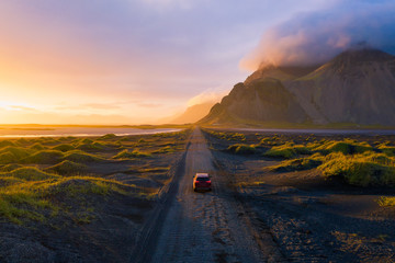 Wall Mural - Gravel road at sunset with Vestrahorn mountain and a car driving, Iceland