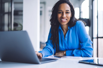 Confident ethnic businesswoman using laptop at work
