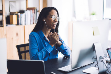 Joyful African American woman videoconferencing on computer with headphones
