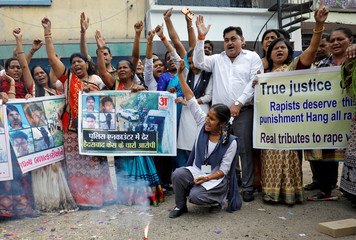 People shout slogans as they celebrate after police shot dead four men suspected of raping and killing a 27-year-old veterinarian in Telangana, in a residential area in Ahmedabad