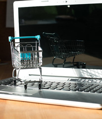 Shopping online concept - shopping cart or trolley on a laptop keyboard. Shopping service on The online web.