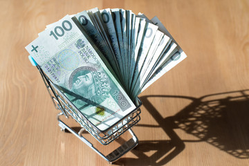 Shopping cart filled with polish zloty - banknotes - currency, money in shopping cart