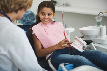 Joyful smiling girl visiting her professional dentist