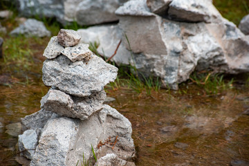 Stones are balancing on each other against the background of water is close