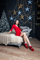 Printed kitchen splashbacks Artist KB Young attractive woman in a red dress is sitting on the bed against the background of the New Year tree. christmas background