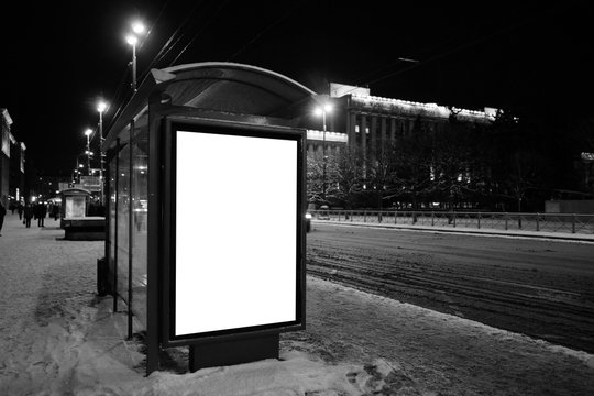 Vertical billboard in the bus stop. bus stop in the winter at night in the city. Ad design MOCKUP with white field. black and white