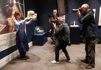 "A Sotheby's employee poses for photographers with a prototype of an Imperial Stormtrooper helmet 1976, estimated at £30,000-£60,000 created for the first ""Star Wars"" film during a photocall at Sotheby's in London"