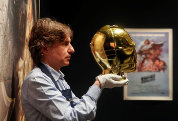 "A Sotheby's employee poses with a ""Return of the Jedi"" promotional C-3PO Helmet 1983, estimated at £15,000-£25,000 created by George Lucas' visual effects company during a photocall at Sotheby's in London"