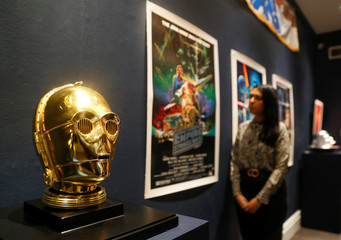 "A Sotheby's employee is seen near a ""Return of the Jedi"" promotional C-3PO Helmet 1983, estimated at £15,000-£25,000 created by George Lucas' visual effects company during a photocall at Sotheby's in London"