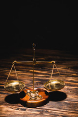 golden scales of justice on wooden table on black background
