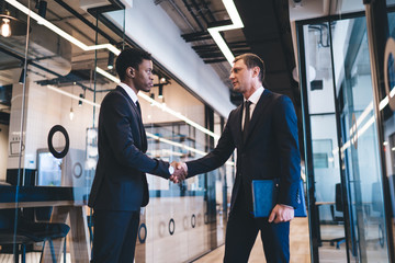 Multiethnic independent startuppers shaking hands at office Fotoväggar