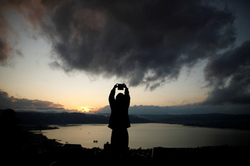 A woman takes photos of Lake Suwa at dusk at Tateishi Park in Suwa