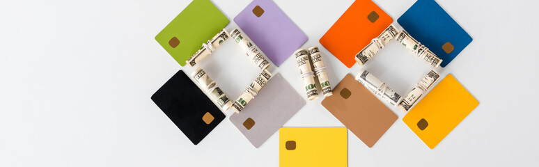panoramic shot of multicolored credit card templates near cash rolls on white