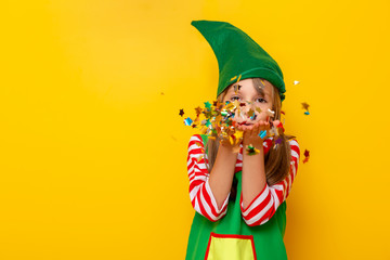 Little girl in Santa helper costume blowing away a handful of colorful confetti