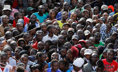 Crowds of people watch as rescue teams search the scene where a building collapsed in Nairobi