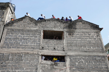 People watch from the roof of a building as rescue teams search the scene where a building collapsed in Nairobi