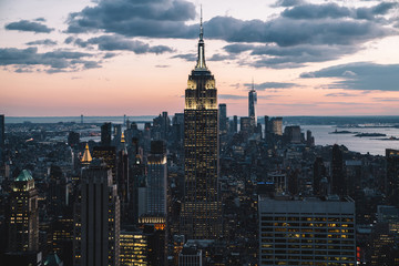 Fototapeten New York Aerial view of glowing skyscraper with bright buildings around located in Manhattan district of New York city. Famous landmark Empire State Building, beautiful skyline background, perfect wallpaper
