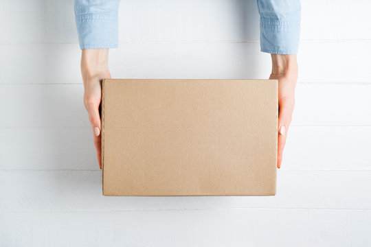 Rectangular cardboard box in female hands. Top view, white background