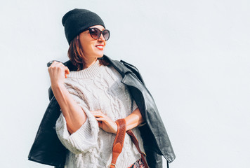 Wall Mural - Smiling female dressed fashion style warm knitted sweater with black leather biker jacket and Beanie Hat with flap bag trendy sunglasses posing on the white wall background.