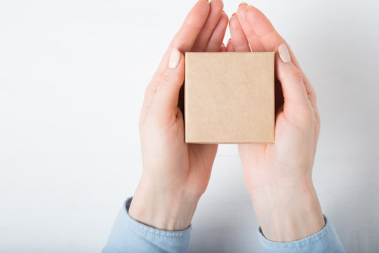 Small square cardboard box in female hands. Top view, white background