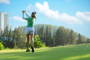 Asian  Sporty woman golfer player doing golf swing tee off on the green, people presumably does exercise. Healthy Sport Lifestyle Concept..